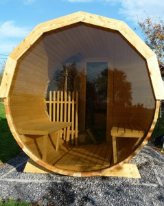 Wooden barrel sauna with glass wall.