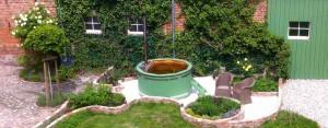 Hot tub in a garden. Bain nordique dans un jardin. Hot tub in een tuin.